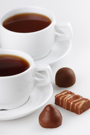 comfit: Cup of tea with sweets on white background