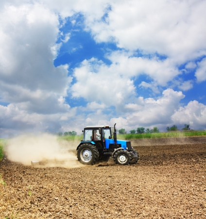 Farming blue tractor in a field, agricultural scene in summer photo