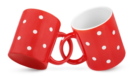Two coupled red polka dot mugs isolated on white with clipping path photo