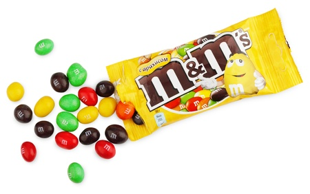 deliciously: Closeup of unwrapped M&Ms milk chocolate candies made by Mars Inc. isolated on white background with clipping path