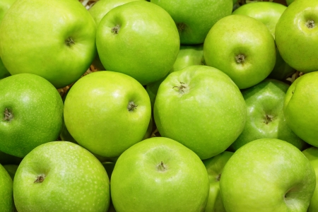 Closeup of many green juicy apple fruits in market photo