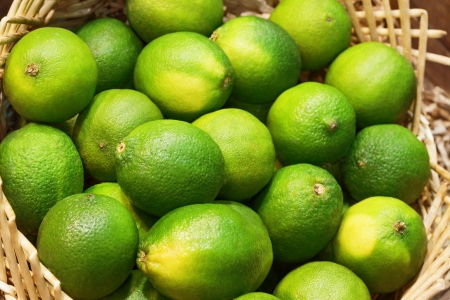 Closeup of many green juicy lime fruits in basket photo