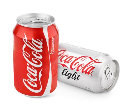 cola canette: Gros plan de canettes d'aluminium de rouge Coca-Cola Classique et lumière produite par la société Coca-Cola isolé sur fond blanc avec chemin de détourage. Studio shot Éditoriale