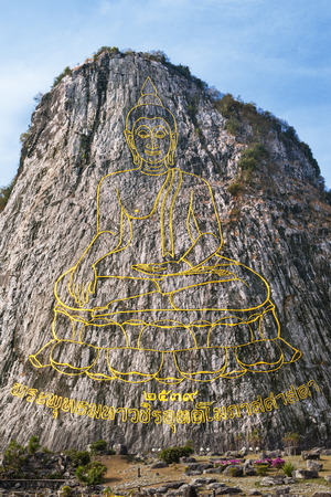 Carved buddha image from gold on the cliff at Khao Chee Jan, Pattaya, Thailand photo