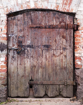 Closed big old door with rusty key with clipping path photo