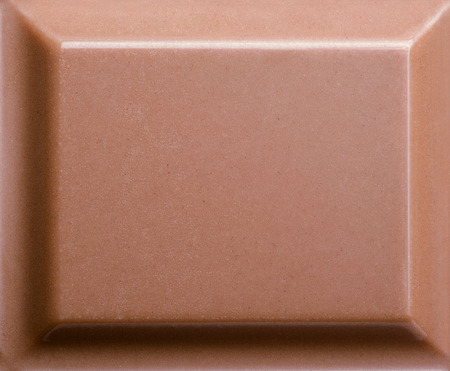 Top view of milk chocolate piece. Closeup photo