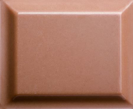 Top view of milk chocolate piece. Closeup photo
