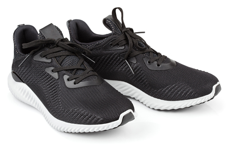 Pair of new unbranded black sport running shoes, sneakers or trainers isolated on white background with clipping path