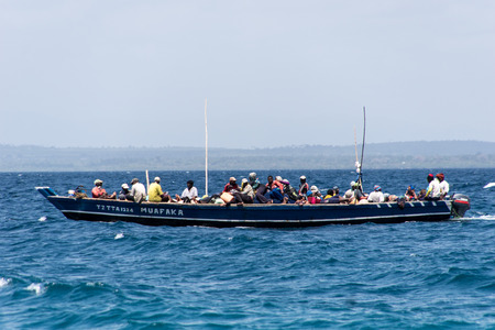 tanga: A small boat crowded with local fishermen, sailing in the Indian ocean near Tanga, Tanzania, East Africa