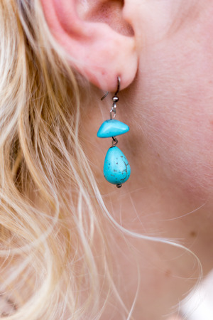 pierce: A girl with blue turquoise earrings on her ear Stock Photo