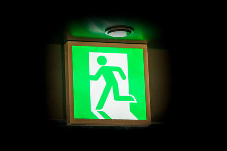 blacked: Emergency exit symbol glowing green in the blacked out background