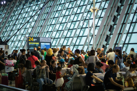 delay: Shanghai, China - circa August 2016: passengers waiting at crowded departure gate after delay, Shanghai Pudong airport, China. Shanghai Pudong Airport is one of the largest airport in Asia.