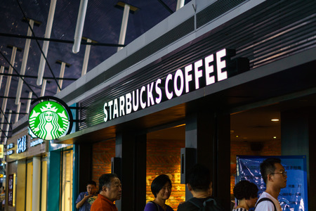 the mainland: Shanghai, China - circa June 2016: Starbucks Coffee shop with customers waiting in line in Shanghai airport, China. Starbucks Coffee is an American coffeehouse chain operating worldwide including over 2000 shops in the mainland China.