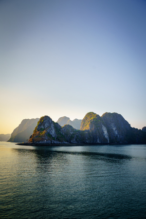 Halong Bay sunset cruise view (Descending Dragon Bay) at the Gulf of Tonkin of the South China Sea Vietnam. Landscape formed by karst towers-isles on blue sky background.