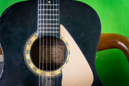 old acoustic guitar on green paint wall background - vintage grunge style with chipped fingerboard