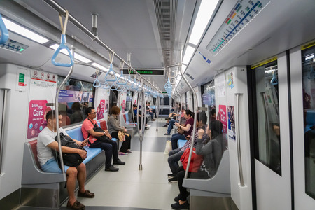 Singapore - January 2019: Passengers in Singapore Mass Rapid Transit (MRT) train. The MRT has 102 stations and is the second-oldest metro system in Southeast Asia.