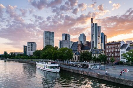 Frankfurt, Germany - July 2019:  city skyline and the river of Frankfurt am Main during beautiful sunset.