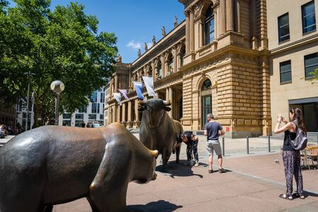 Frankfurt, Germany - July 2019: : Stock exchange building and tourists around bull and bear sculpture. Frankfurt Stock Exchange is the world's 10th largest stock exchange by market capitalization