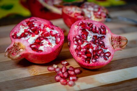 pomegranate fruit sliced on a wooden cutting board. Ripe pomegranate closeup with selective focus