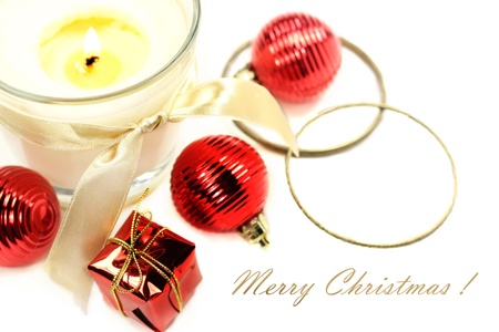 Christmas still life with lit candle, present and balls decoration on white background. Free space for text