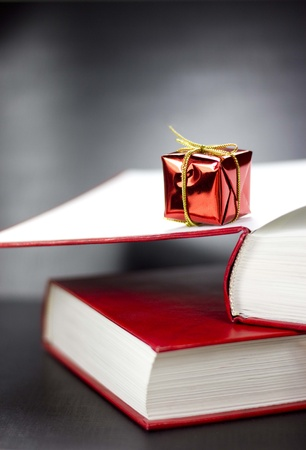 Close up of side view of two red books and small red present lying on them. Black background photo