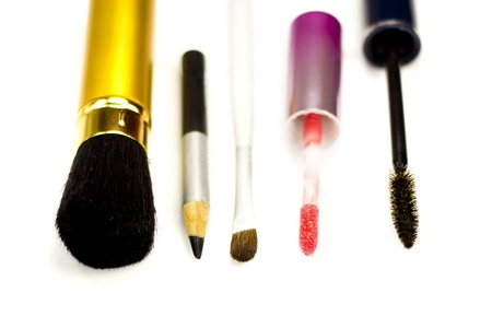 Close-up of eyeliner, applicator for lip gloss and brushes for eye-shadows, brusher and mascara on a white background photo