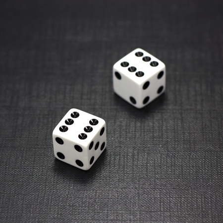 craps: Two white dices on a black background