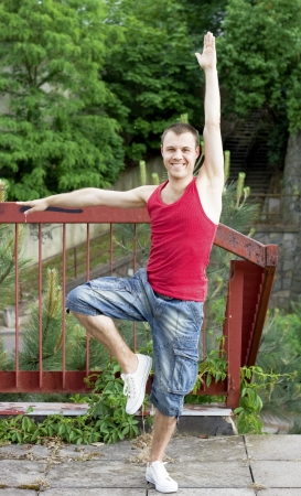 A smiling guy doing gymnastics, outdoors background photo