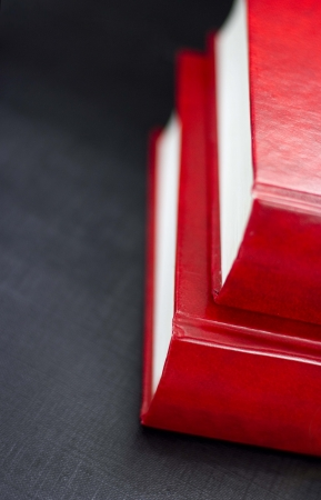 Side view of two red books on a black background