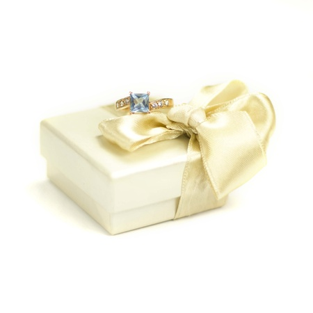 Closeup of golden ring with topaz and fair gift box with bow on a white background Stock Photo - 13969711