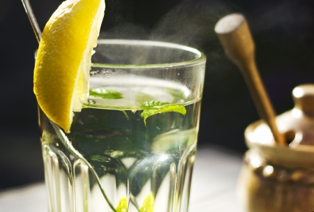 warm water: Glass of hot tea with a fresh peppermint and lemon and a honey pot