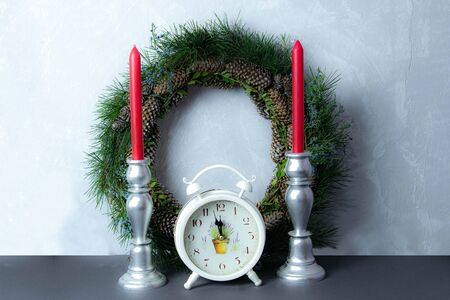 Xmas or new year composition with holiday decoration - candlestick with candles on the fireplace and vintage clock Stock Photo