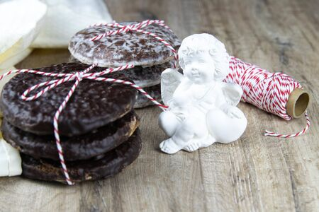 Chocolate ginger biscuits bandaged with red-and-white thread with cinnamon