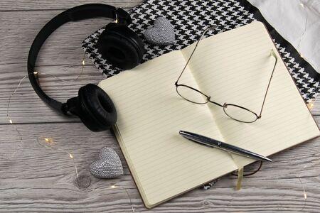 Bolso de cuero, libreta limpia en blanco, bolígrafo, gafas, reloj sobre un fondo de madera, vista superior. Espacio libre para texto. Foto de archivo
