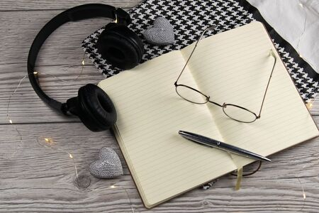 Leather handbag, clean blank notepad, pen, glasses, watch on a wooden background, top view. Free space for text. Фото со стока