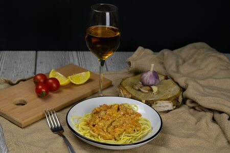 Spageti bolognese on a beautiful background next to stand a glass of white wine and clock. Фото со стока