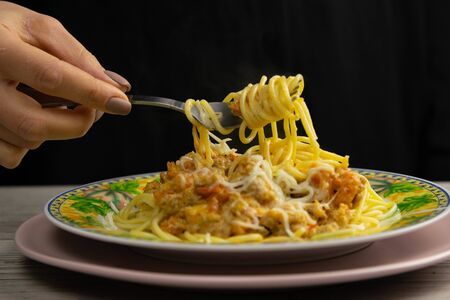 The womans hand is sprinkled with spices of sgeti bolognese plate stands on a beautiful wood background.