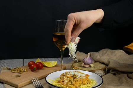 The womans hand is sprinkled with cheese of spaghetti bolognese plate stands on a beautiful wood background. Фото со стока