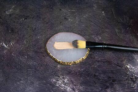 Makeup foundation brush blur cream black background.