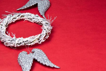 A door wreath of branches decorated with artificial snow. Nearby are angel wings of silver color. Everything stands on a red background with a place for text. Top views