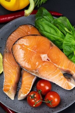 Two fresh raw salmon steaks with vegetables and spices: rosemary, tomatoes, peppers, basil, lemon and olive oil on a gray plate on black background. The concept of a healthy diet diet. Top views