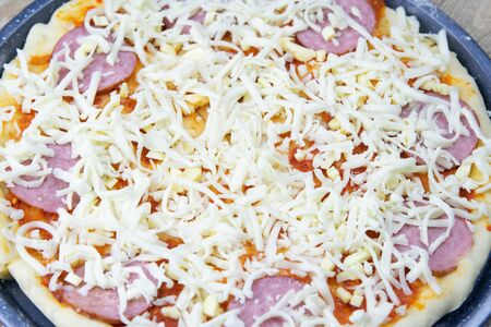 Prepared preparation for pizza with salami covered with tomato sauce, mozzarella, salami