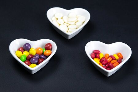 Heart shaped saucer filled with colorful candies on a black background. Valentine's Day illustration. Top views