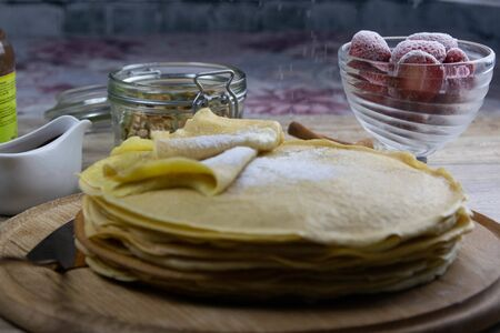 Pancakes with butter and chocolate on a wooden round board on the wooden background with strawberry and seeds