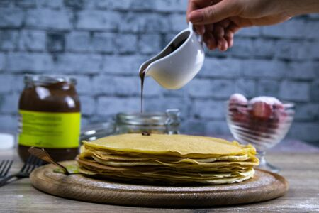 Pancakes with butter and chocolate on a wooden round board on the wooden background with nutella, strawberry and seeds hand pours chocolate