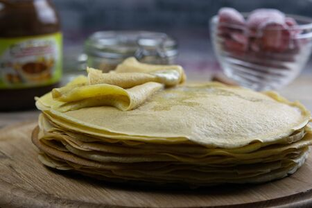 Pancakes with butter and chocolate on a wooden round board on the wooden background with nutella and strawberry