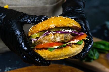 Woman's hands in black rubber gloves are holding juicy bun burger with meat cutlet, lettuce, tomato, shredded cheese and marinated cucumber. Top views