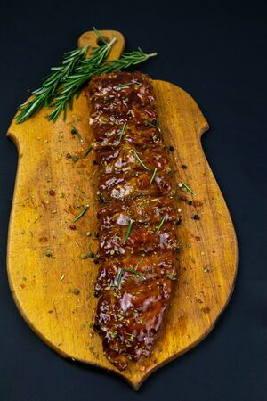 Barbecue Pork Spare Ribs with rosemary as top view on an old cutting board top views