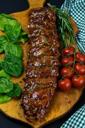 Barbecue Pork Spare Ribs as side view with basil and tomatoes and hot pepper with cracker on an old cutting board top views Banco de Imagens