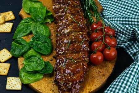 Barbecue Pork Spare Ribs as side view with basil and tomatoes and hot pepper with cracker on an old cutting board top views 写真素材
